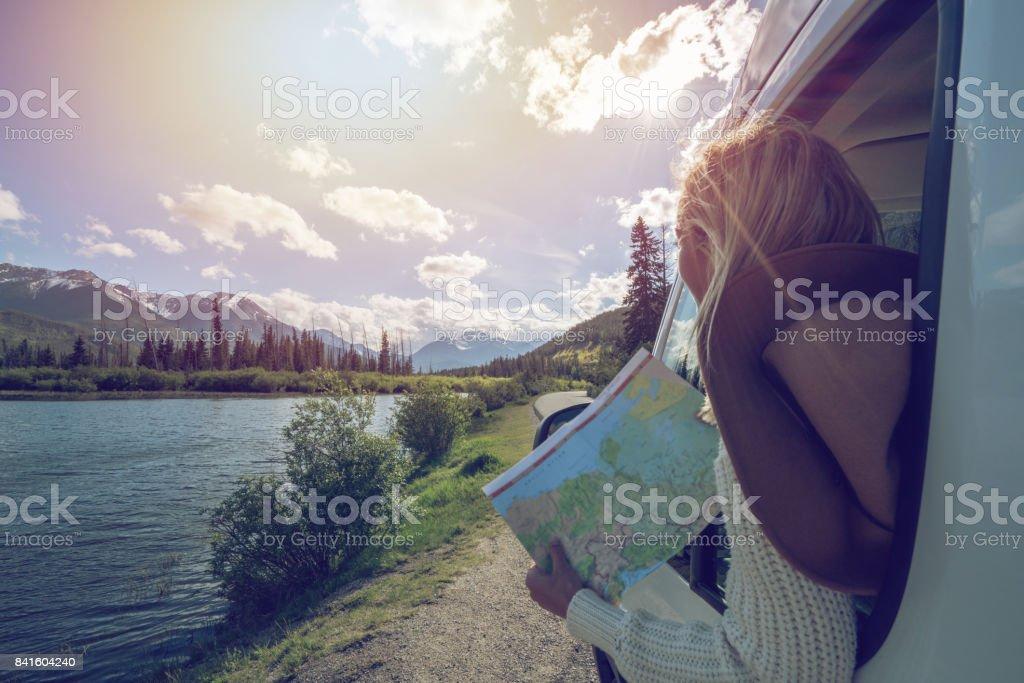 Mujer joven mira de ruta cerca de lago de montaña - foto de stock
