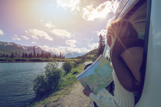 Young woman looks at road map near mountain lake stock photo