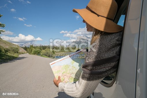 841604240 istock photo Young woman looks at road map near mountain lake 841680804