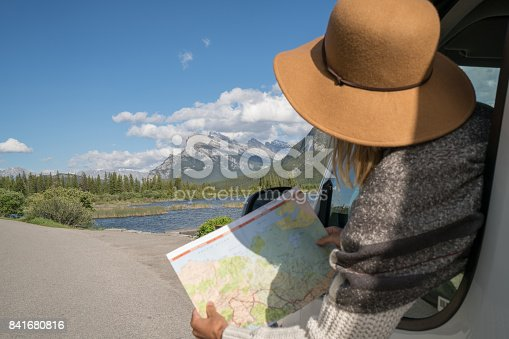 841604240 istock photo Young woman looks at road map near mountain lake 841680816