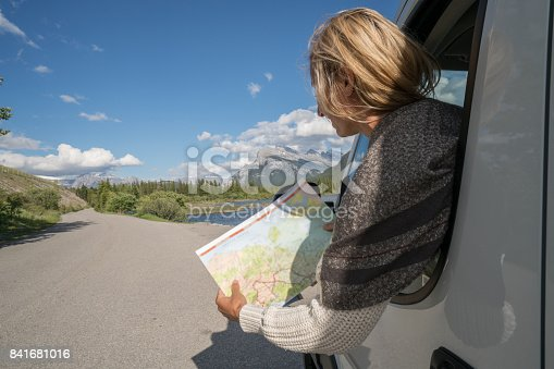 841604240 istock photo Young woman looks at road map near mountain lake 841681016
