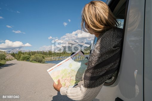 841604240 istock photo Young woman looks at road map near mountain lake 841681040