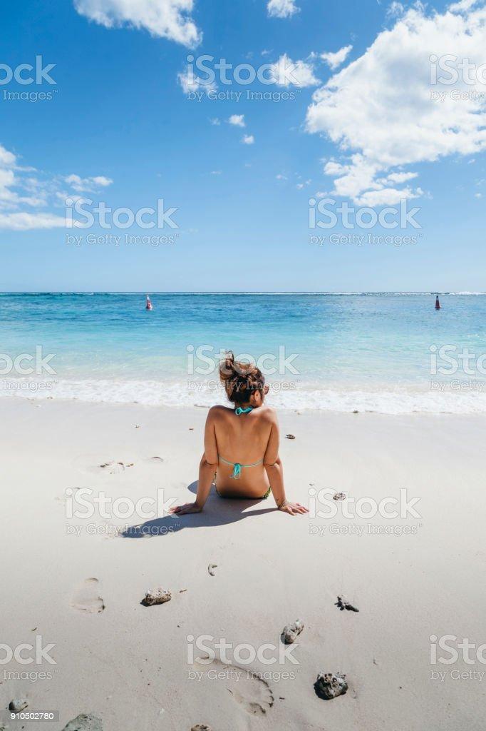 Junge Frau sieht am Horizont sitzen auf einem Strand von Mauritius im Sommer – Foto