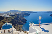 Young woman stands on a hill and looks at the marine landscape of Santorini, Greece