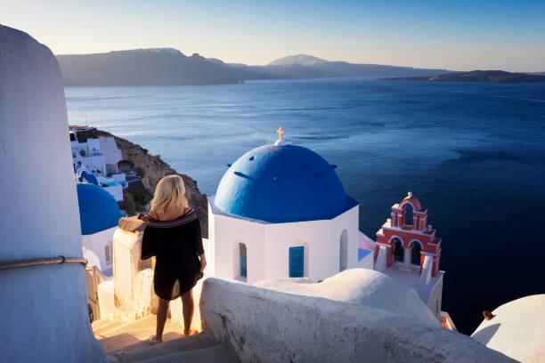 Junge Frau schaut auf die Meereslandschaft, Santorini, Oia, Griechenland – Foto