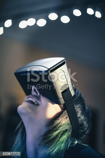 599693172istockphoto Young woman looks fascinated into Virtual Reality Headset 520877772