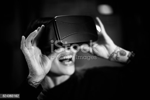 599693172istockphoto Young woman looks fascinated into Virtual Reality Headset 524383162