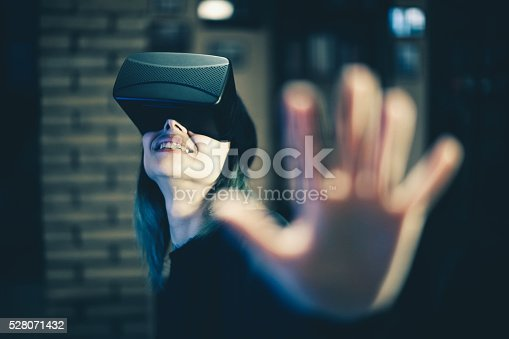 599693172istockphoto Young woman looks fascinated into Virtual Reality Headset 528071432