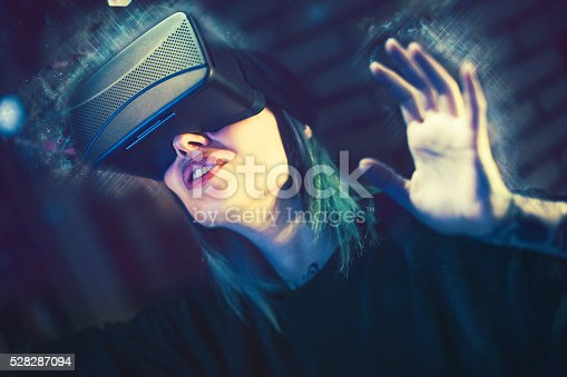 599693172istockphoto Young woman looks fascinated into Virtual Reality Headset 528287094