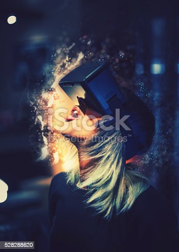599693172istockphoto Young woman looks fascinated into Virtual Reality Headset 528288620