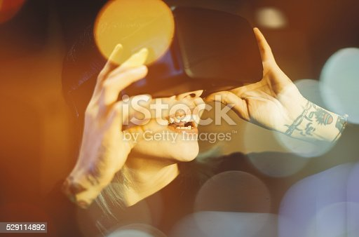 599693172istockphoto Young woman looks fascinated into Virtual Reality Headset 529114892