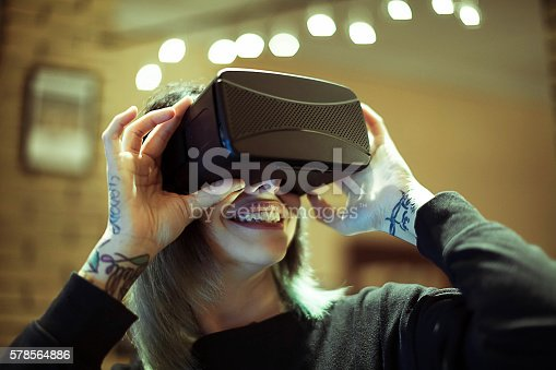 599693172istockphoto Young woman looks fascinated into Virtual Reality Headset 578564886
