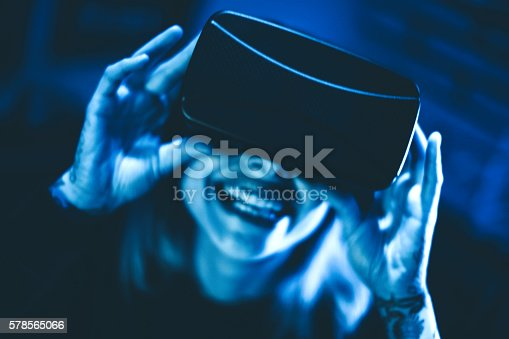 599693172istockphoto Young woman looks fascinated into Virtual Reality Headset 578565066
