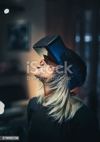 599693172istockphoto Young woman looks fascinated into Virtual Reality Headset 578565236