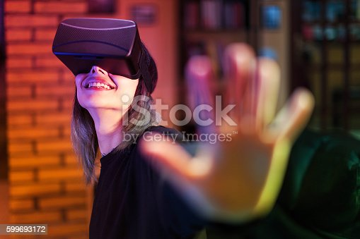 istock Young woman looks fascinated into Virtual Reality Headset 599693172