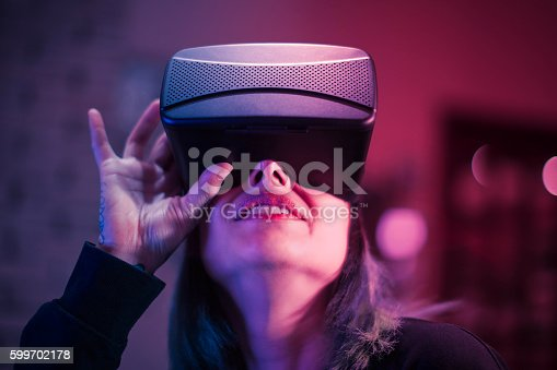 599693172istockphoto Young woman looks fascinated into Virtual Reality Headset 599702178