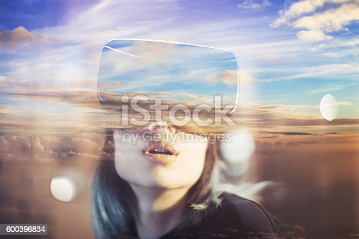 599693172istockphoto Young woman looks fascinated into Virtual Reality Headset 600396834