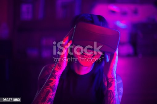 599693172istockphoto Young woman looks fascinated into Virtual Reality Headset 969571880