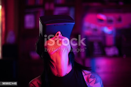 599693172istockphoto Young woman looks fascinated into Virtual Reality Headset 969662448