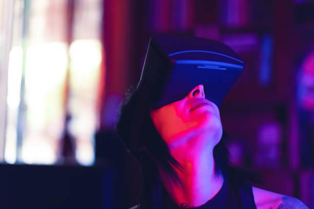 young woman looks fascinated into virtual reality headset - ritratto 360 gradi foto e immagini stock