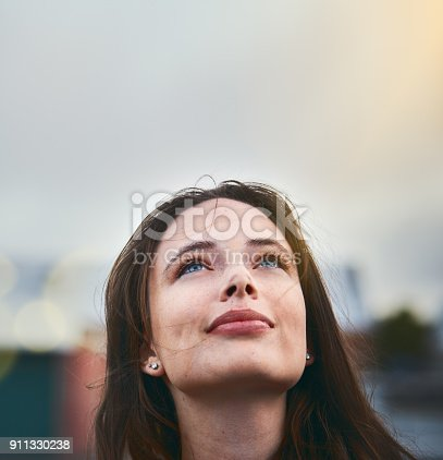 Young woman looks hopeful as she raises her eyes towards the sky.