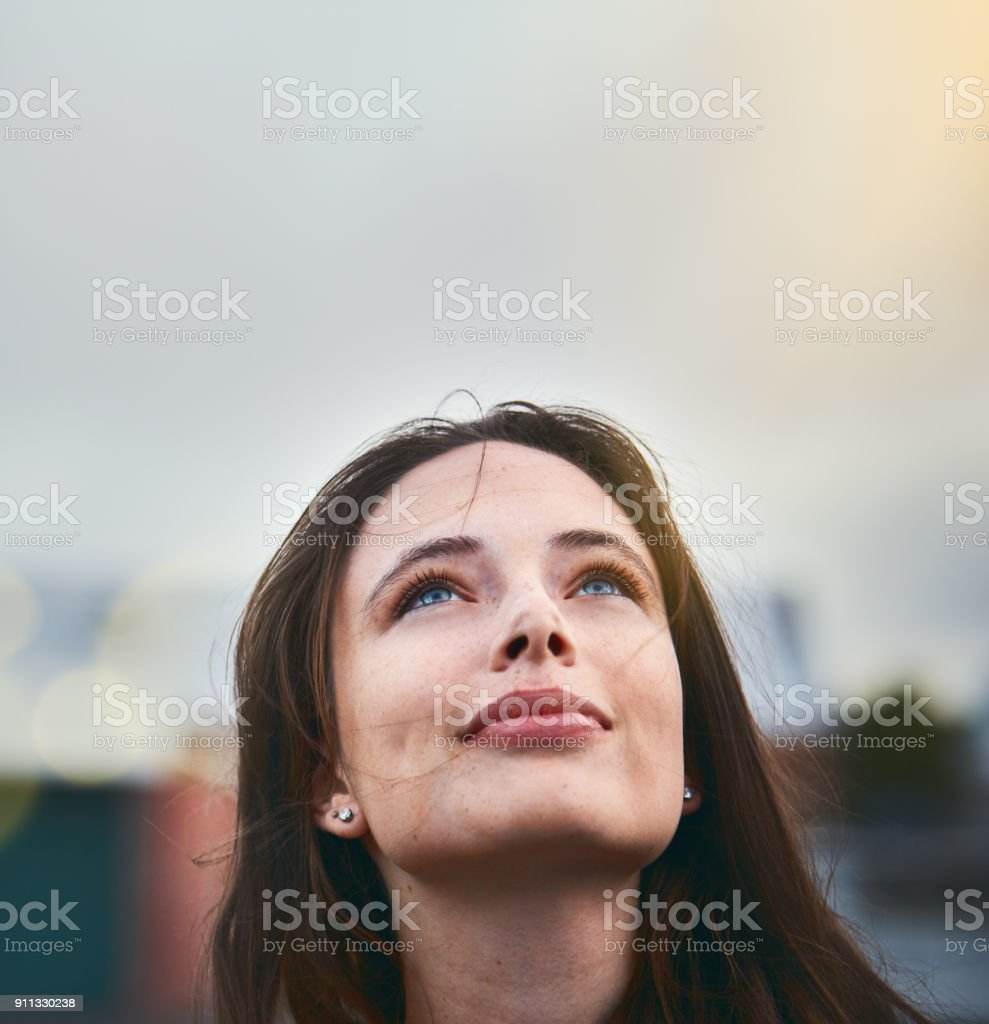Young woman looks hopeful as she raises her eyes towards the sky stock photo