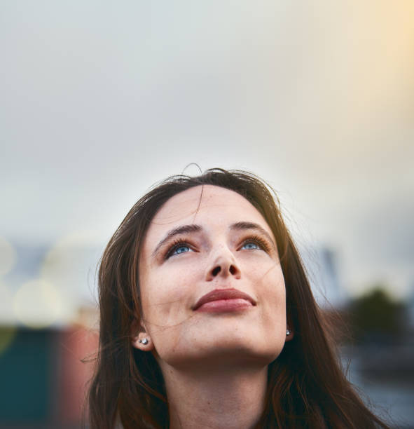 Young woman looks hopeful as she raises her eyes towards the sky - foto stock