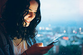 istock young woman looks into smartphone, illuminated city skyline in background 472105512