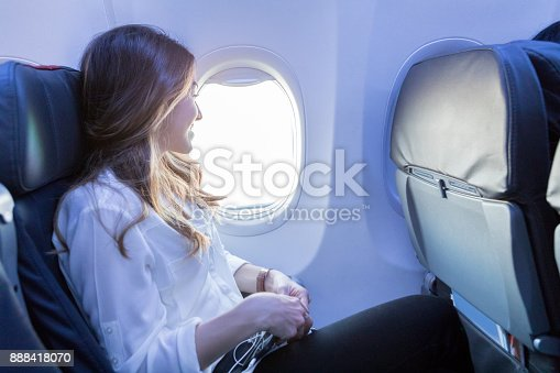 In this side view, a smiling young woman enjoys looking out the window of her aircraft as she awaits arrival to her destination.