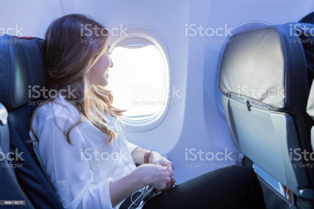 Young woman looks out aircraft window during flight stock photo