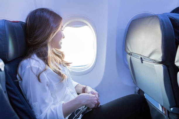 young woman looks out aircraft window during flight - foto di sedili aereo foto e immagini stock