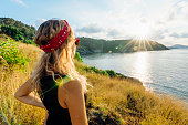 istock Young woman looks out from hill in grasses above the sea 1070953002