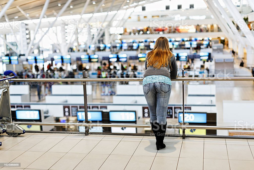 Young woman looks out over busy check-in section at airport royalty-free stock photo
