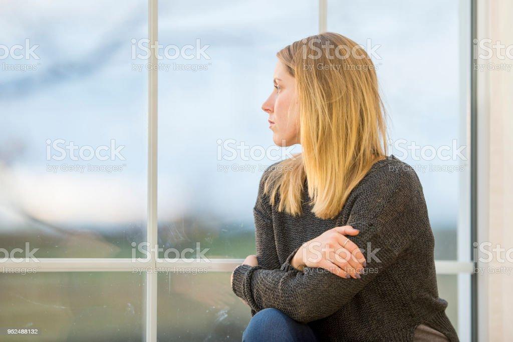 Junge Frau schaut nachdenklich aus dem Fenster – Foto