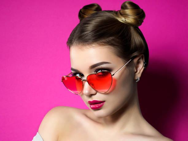 junge frau schaut über herzförmige brille - lustige augenbrauen stock-fotos und bilder