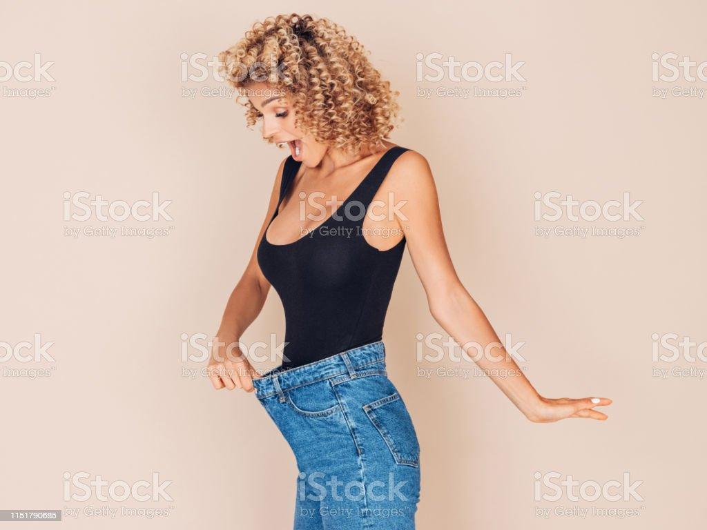Young woman losing weight - Foto stock royalty-free di Abbigliamento casual