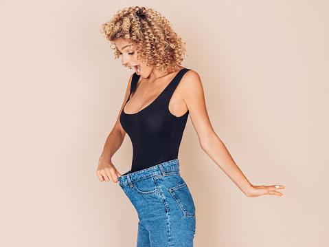 Young Woman Losing Weight - Fotografie stock e altre immagini di Abbigliamento casual