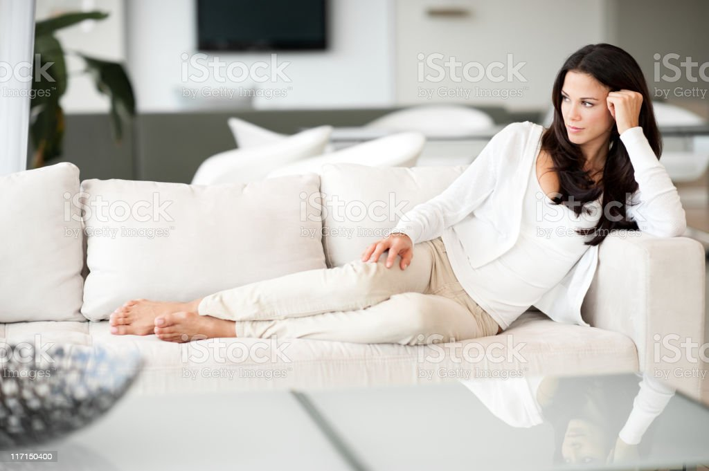 Young Woman Lounging in Living Room on Couch royalty-free stock photo