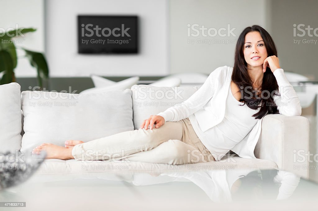 Young Woman Lounging in Living Room on Couch stock photo