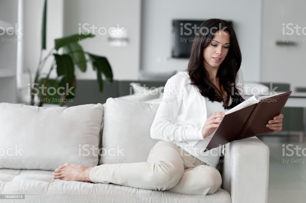 Young Woman Lounging in Living Room Reading Book royalty-free stock photo