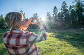 Young woman loving nature making heart shape finger frame on green scenery of pines and grass at sunset