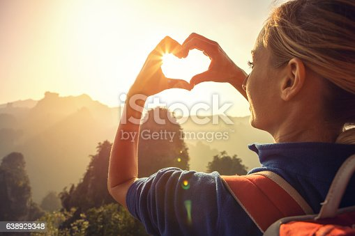 Young woman hiking in the Zhangjiajie National Forest park, makes a heart shape finger frame. Love nature wanderlust sharing concept.