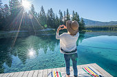istock Young woman loving sunrise at mountain lake 848136270