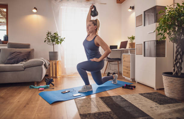 Young woman lunging with kettlebell on yoga mat in living room stock photo