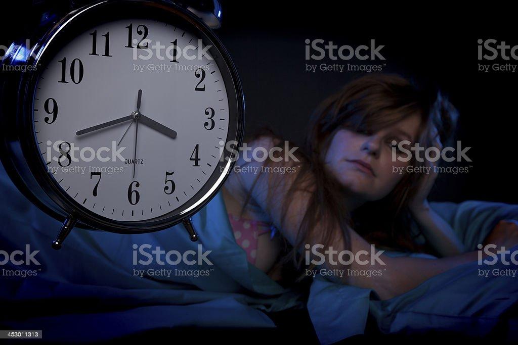Young woman lying awake stock photo