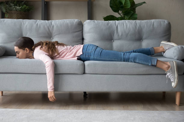 Young woman lying buried her face in sofa feels tired stock photo