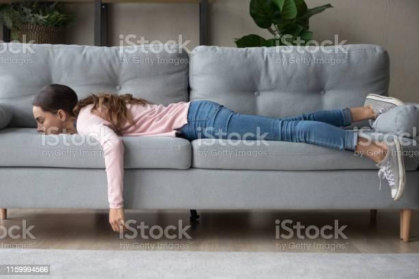 Jonge Vrouw Liegen Begraven Haar Gezicht In Sofa Voelt Moe Stockfoto en meer beelden van Aanraken