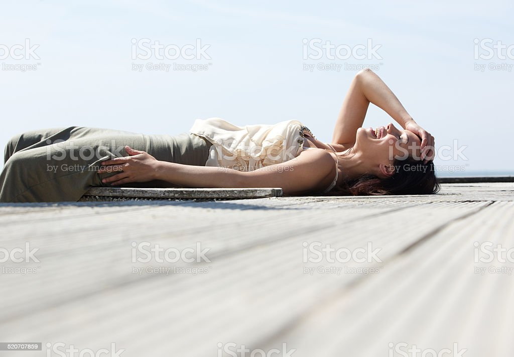 Young woman lying down and laughing outdoors stock photo