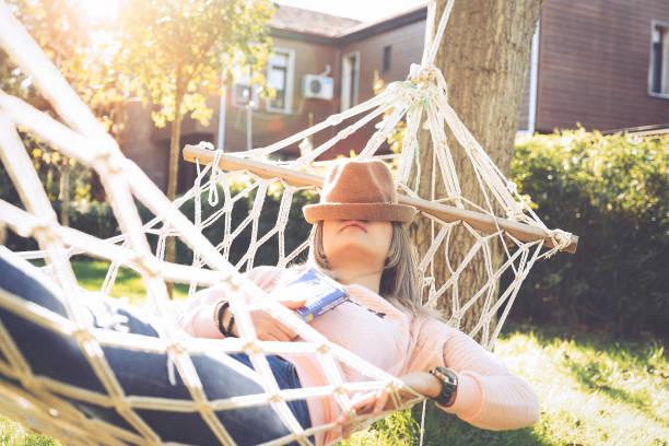 jeune femme couchée et dormant sur un hamac - faire un somme photos et images de collection