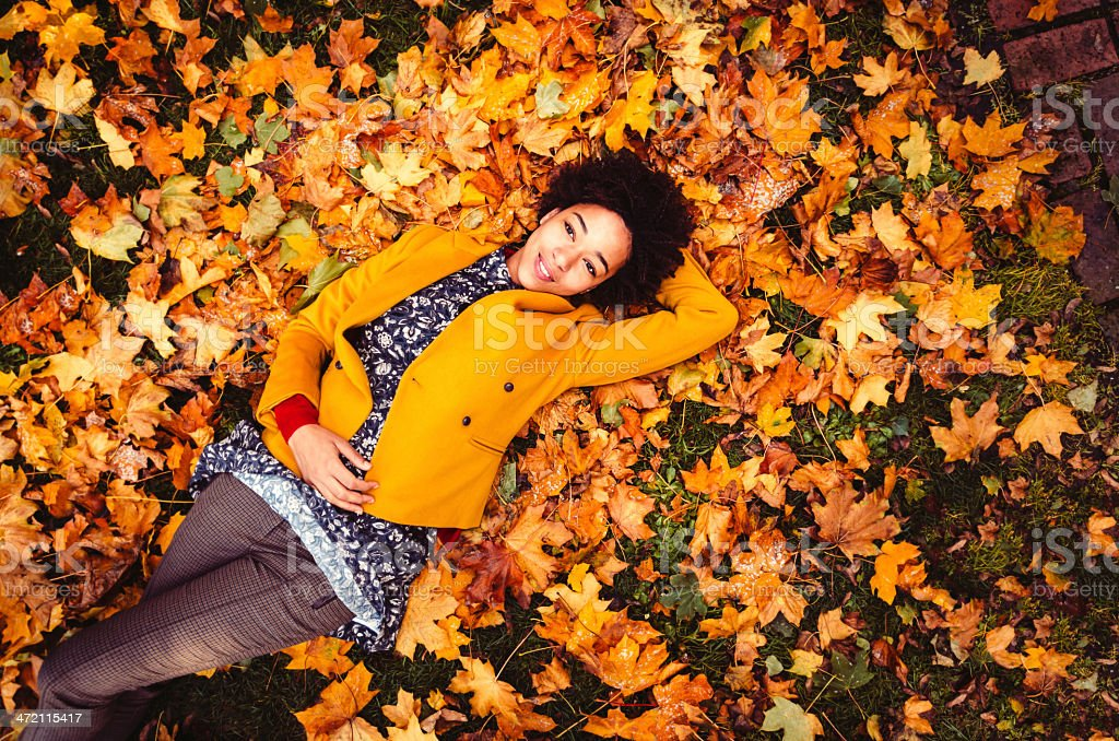 Young Woman Lying Down On Yellow Leaves stock photo